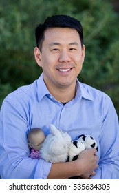Blissful Asian Modern Family Portrait: Dad Holding His Daughter's Stuff Animals