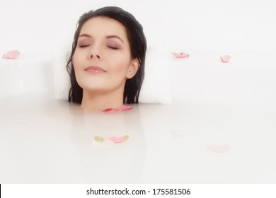 Blissful beautiful young woman pampering herself soaking in a hot bath with just her face visible above the soapy water as she relaxes with a serene expression and her eyes closed