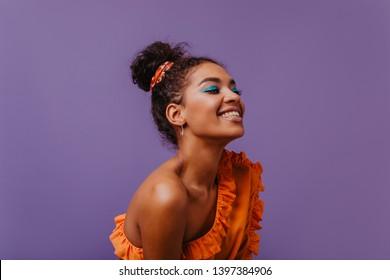 Blickvolle schwarze Frau im Sommerkleid, die auf violettem Hintergrund lacht. Adorable afrikanische Mädchen in orangefarbenem Outfit posiert mit fröhlichem Gesichtsausdruck.