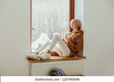 Blissful blond woman funny fur slippers warming, relaxing sittng on window sill with hot coffee or tea in empty cozy home in sunny winter day.