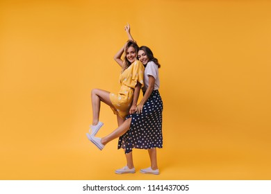 Blissful brunette girl in long skirt posing with her sister. Indoor shot of spectacular female friends isolated on yellow background.