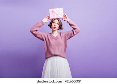 Blissful european female model holding birthday present over head and smiling. Studio shot of fascinating girl with short haircut posing with gift on coloful background.