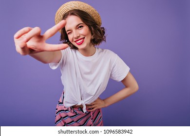 Blissful european girl with dark eyes posing in trendy straw hat. Indoor photo of sensual female model with short hair standing on purple background and laughing.