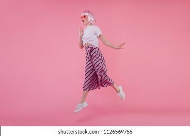 Blissful european young woman in elegant white sneakers jumping during phtooshoot. Studio portrait of joyful lady wearing peruke dancing on pink background.