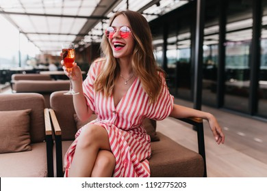 Blissful fair-haired girl spending summer day in restaurant. Happy european woman wears striped dress drinking champagne and smiling.