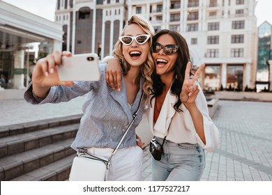 Blissful fair-haired woman in sunglasses making selfie with friend. Dreamy brunette girl expressing positive emotions in spring day.