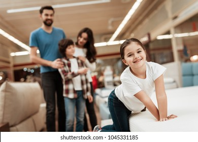 Blissful family buys new orthopedic mattress in furniture store. Happy Couple choosing mattresses in store. Orthopedic mattress, for comfortable sleep and healthy posture.