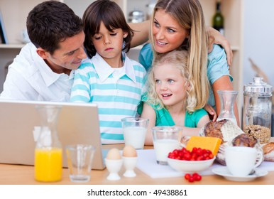 Blissful family using laptop during the breakfast in the kitchen