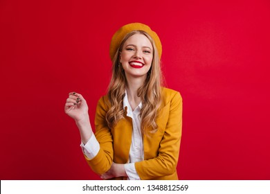 Blissful french female model laughing at camera. Front view of blonde girl in beret isolated on red background.