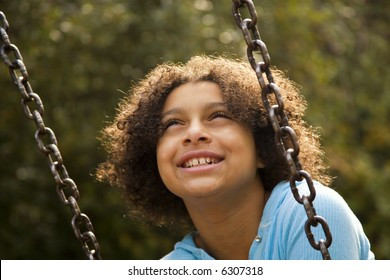 blissful girl on a swing in the park