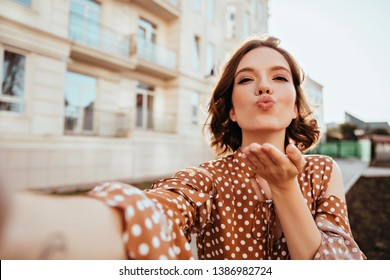 Blissful girl in vintage attire making selfie on the street. Gorgeous caucasian lady in brown outfit sending air kiss to camera.