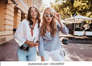 Blissful girls posing with smile in town. Outdoor photo of amazing caucasian ladies enjoying weekend.