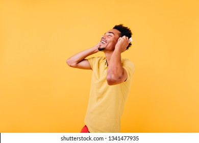 Blissful man with beautiful smile listening music. Indoor shot of african male model in headphones expressing positive emotions.