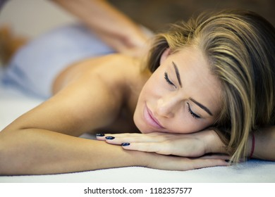 Blissful massage. Woman at a massage in spa center. Close up. Copy space. . Focus is on woman.