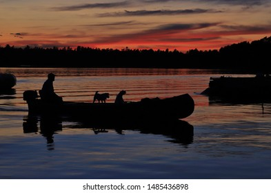 A blissful moment of a man on a motorized canoe with his pair of dogs.  On a lake in Canada at sunset.  Colors in nature, graceful elegance of peace and life.  Inspiration through life wonders.
