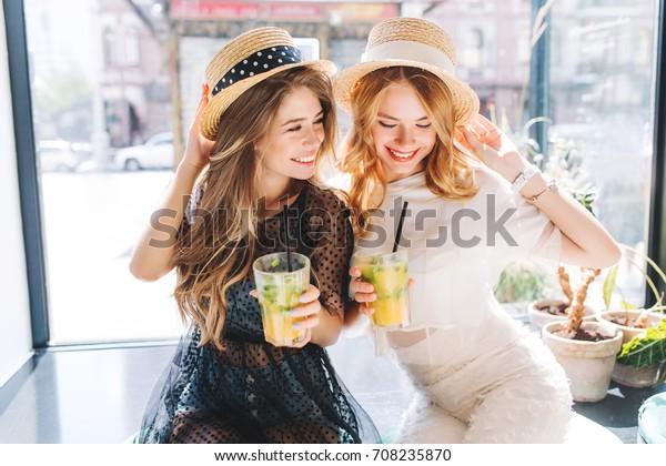 Блаженны симпатичные дамы в модных платьях сидят возле большого окна с бокалами ледяных коктейлей и смеются. Крытый портрет симпатичных модных женщин наслаждается соком после покупок.