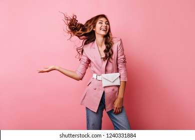Blissful red-haired girl enjoying studio photoshoot. Carefree caucasian lady in pink jacket laughing on pastel background.