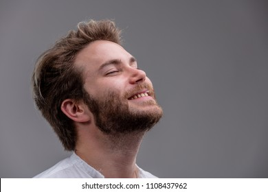 Blissful relaxed bearded young man with his head tilted back, closed eyes and a beaming smile isolated on grey with copy space