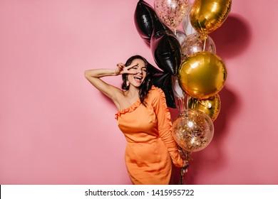 Blissful slim woman dancing at her birthday party. Latin girl in orange dress enjoying event.