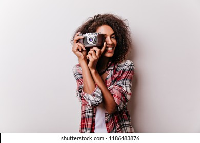 Blissful smiling girl with camera making photos. Indoor shot of attractive female photographer wears checkered shirt.