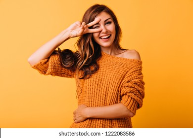 Blissful stylish girl posing with peace sign on yellow background. Studio photo of well-dressed caucasian female model expressing happiness.
