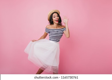 Blissful tanned woman waving hand while dancing in studio. Indoor portrait of pleased brunette girl wears elegant lush skirt.