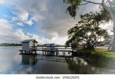 A blissful view of a small modern boatshed on background of the cloudy blue sky