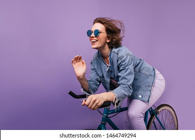 Blissful woman in casual jacket posing on bike. Emotional short-haired girl in sparkle glasses riding on bicycle.