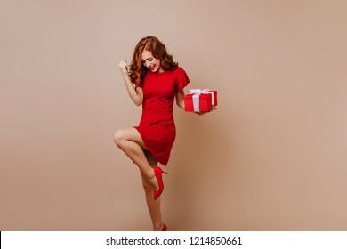 Blissful woman in high heel shoes dancing at christmas party. Joyful birthday girl expressing happiness.