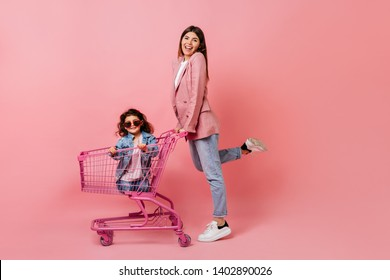 Blissful woman with little daughter posing after shopping. Smiling mother standing near store cart.