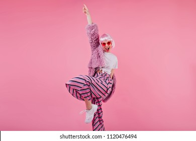 Blissful woman wears striped pants and pink periwig laughing during photoshoot. Confident young lady in sunglasses and fluffy jacket funny dancing.