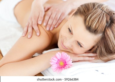 Blissful young woman enjoying a back massage in a spa center
