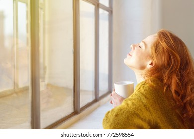Blissful young woman enjoying the sun on her face as she leans on a window sill with her head tilted back and a mug of coffee
