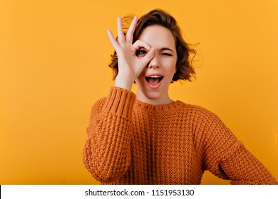 Blissful young woman with pale skin making funny faces during photosoot. Studio shot of pretty curly girl fooling around on bright orange background.