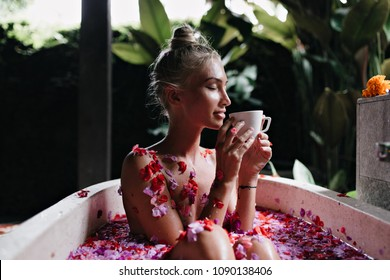 Blissful young woman sitting in bath with eyes closed and drinking hot tea. Portrait of magnificent girl with blonde hair doing spa and enjoying coffee.