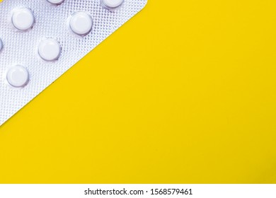 A blister pack of statins, pills tablets for lowering cholesterol on yellow background, prevention and treatment of atherosclerosis and heart disease concept, copy space.