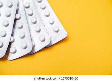 A blister pack of statins, pills tablets for lowering cholesterol on yellow background, prevention and treatment of atherosclerosis and heart disease concept, copy space