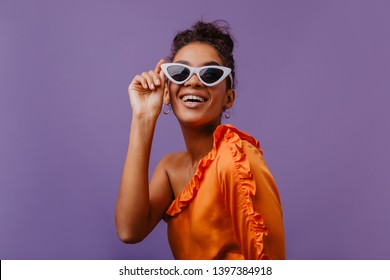 Blithesome african woman in sunglasses chilling during summer photoshoot. Indoor shot of adorable black girl in bright orange clothes.