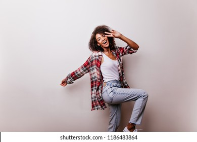 Blithesome attractive girl in jeans dancing on white background. Studio photo of wonderful black lady with happy face expression.