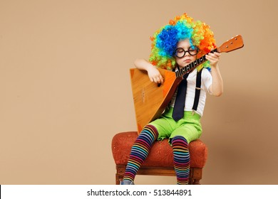 Blithesome children. Happy clown boy in large neon colored wig playing the balalaika. Portrait of kid wearing clown wig and eyeglasses. Brazilian Carnival. Venice Carnival.