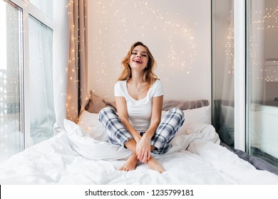 Blithesome girl in white t-shirt laughing during photoshoot at loggia. Indoor shot of sensual blonde lady resting in bed in morning.