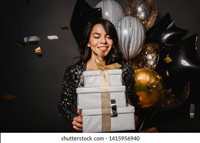 Blithesome latin model celebrating birthday. Indoor photo of gorgeous brunette girl with christmas presents.