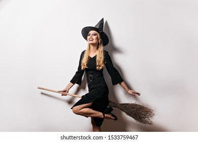 Blithesome long-haired woman having fun in halloween. Cute blonde girl in witch hat smiling at carnival party.