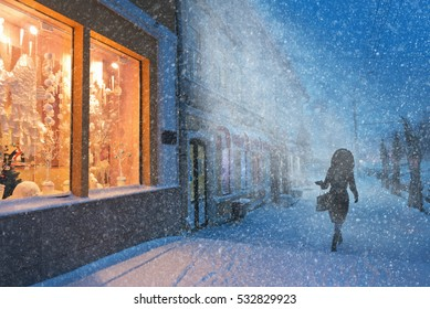 Blizzard in Christmas city girl walks along decorated shop Windows.