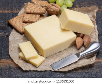 Block of aged cheddar cheese, the most popular type of cheese in United Kingdom and USA, natural cheese made from cow milk