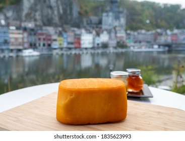 Block of Belgian abbey cheese made with brown trappist beer and view on Maas river near Leffe and Dinant, Wallonia, Belgium