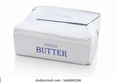 Block of butter from the shop, with fictive logo design. Isolated on white background with shadow reflection. With clipping path. With vector path. Packed piece of butter from supermarket.