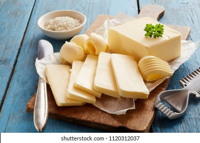 Block of butter sliced on cutting board against blue wooden background