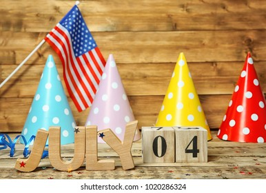 Block calendar and word JULY made of wooden letters on table. Independence day celebration