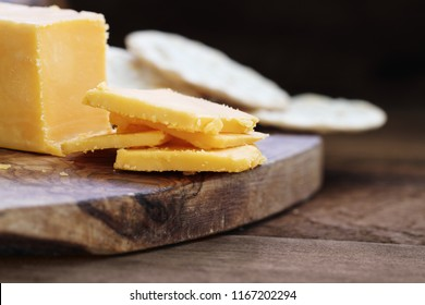 Block of cheddar cheese and slices over a rustic background.. Extreme shallow depth of field with selective focus on cheese. Water crackers in the background.